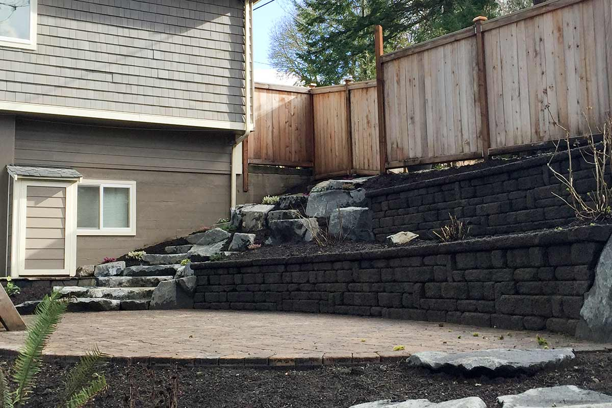 Rear view of the completed project: Celtik Wall retaining wall, Dominion Slate paver patio, rockery with natural stone stairway